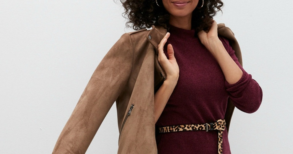woman in burgundy dress and tan jacket