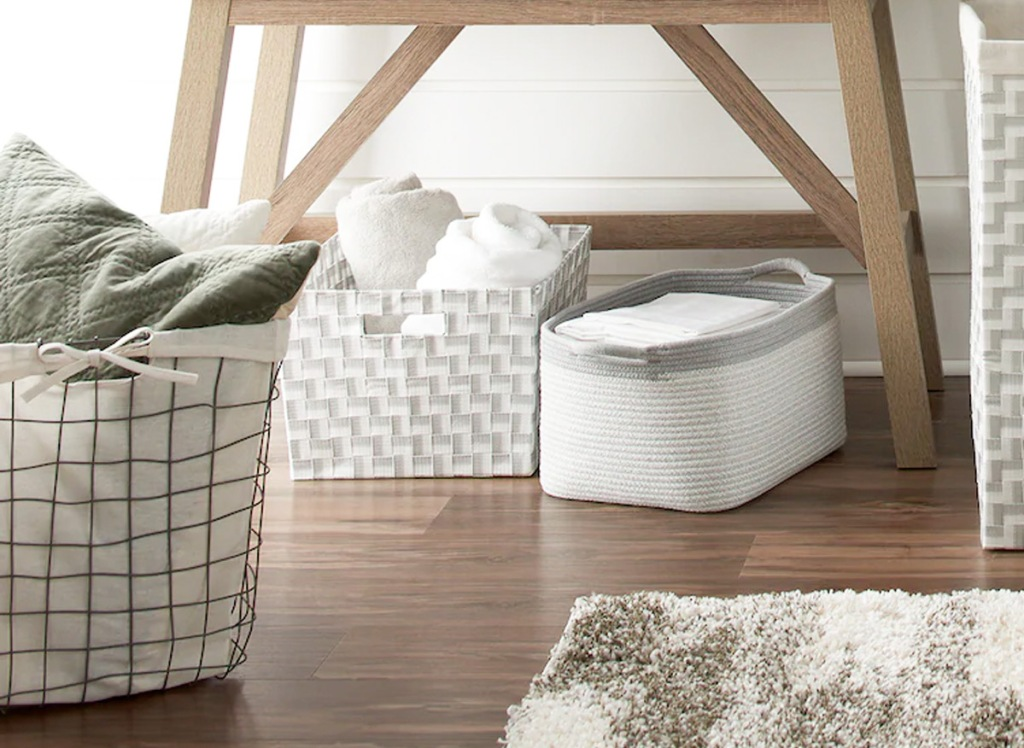 small coiled rope laundry bin on wood floor next to square woven storage bin and wire laundry basket