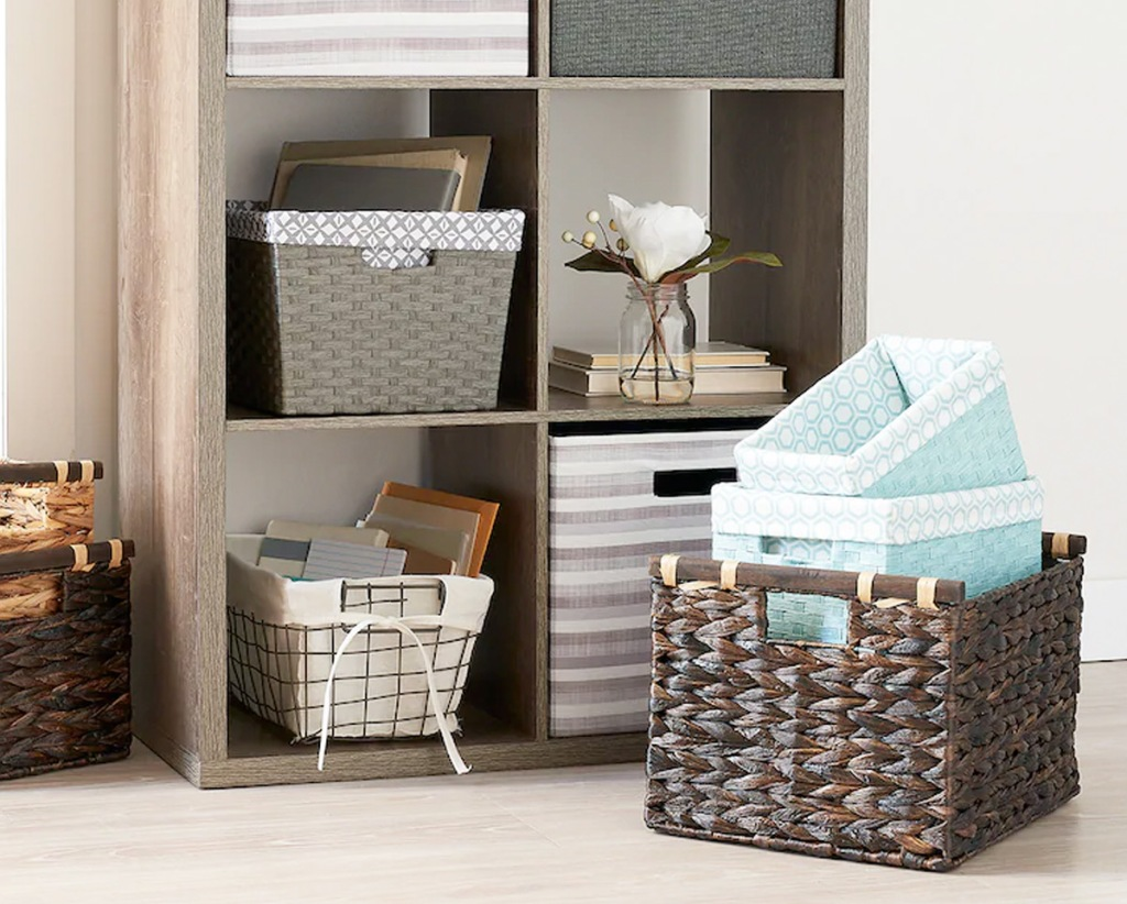 storage cubby with wire and fabric storage bins in each cubby and brown woven storage bin on floor