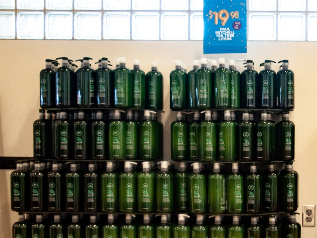 multiple 1 liter bottles of Paul Mitchell shampoo and conditioner in in-store display
