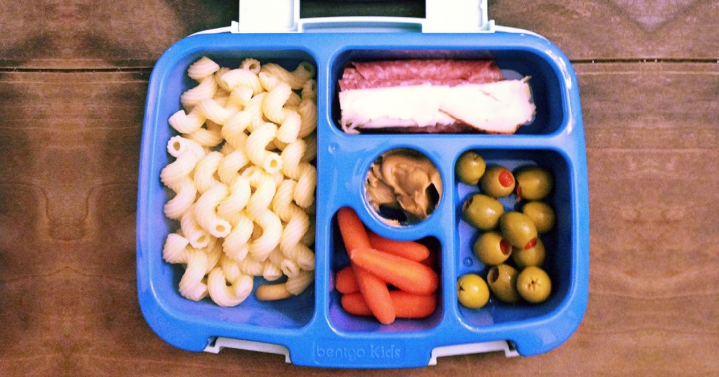 blue purple lunch box filled with food on wood surface
