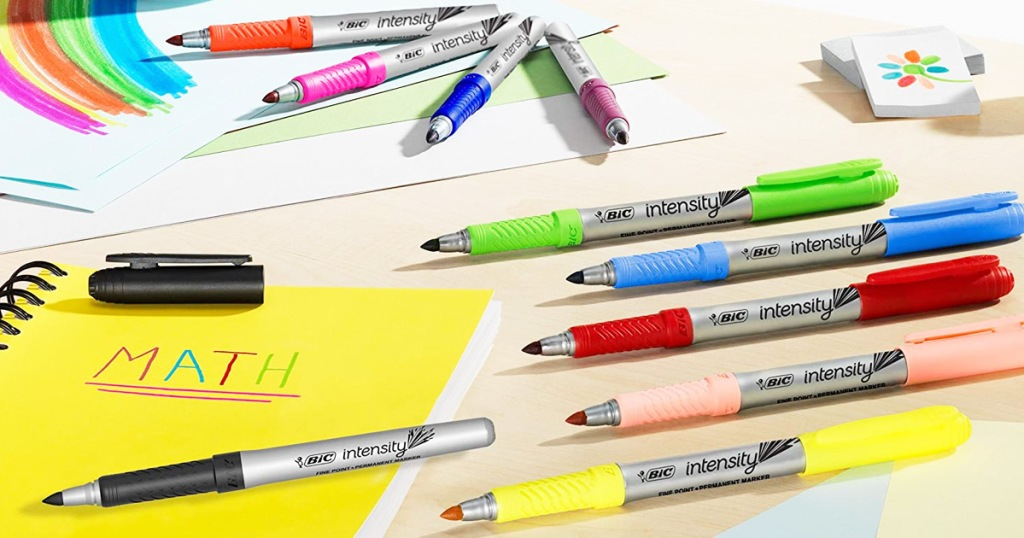bic markers in assorted colors laying on craft table with their caps off