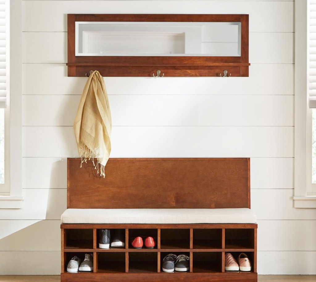 mirrored wall shelf with hooks and scarf hanging above wooden bench with shoe cubbies
