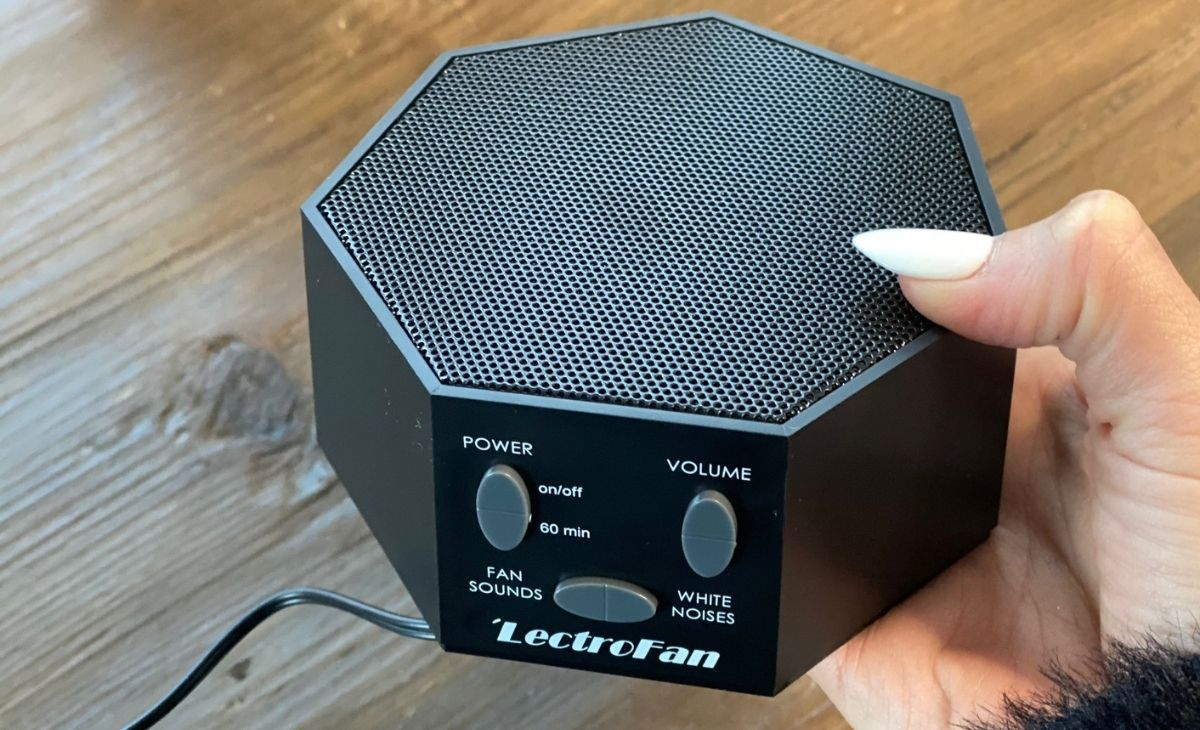 A hand holding a black Lectrofan white noise sound machine