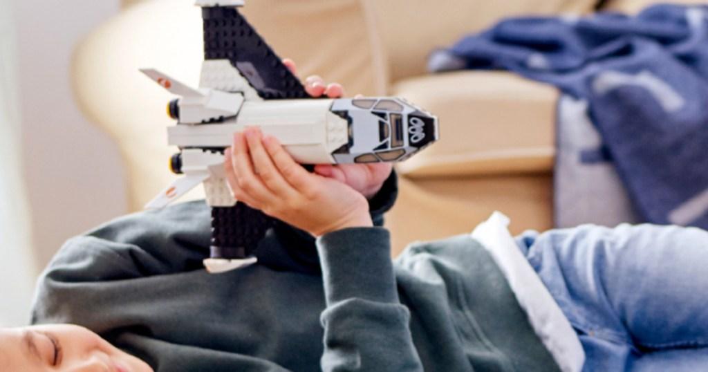 LEGO space shuttle boy laying on ground holding rocket up