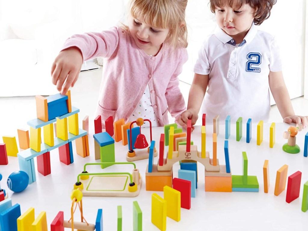 hape dynamo wooden domino set two kids playing