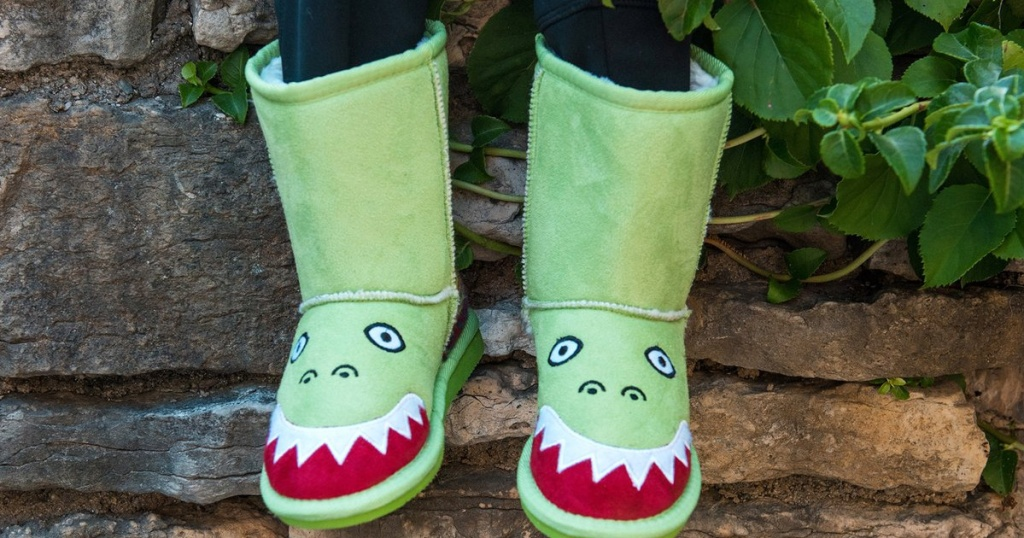 muk luks kids green dinosaur boots sittin on a wall