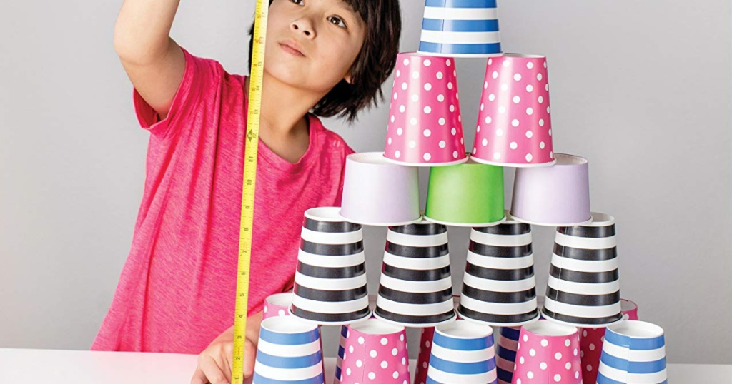 girl measuring a cup tower