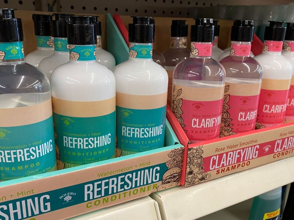 shampoo and conditioner bottles in cardboard trays on store shelf