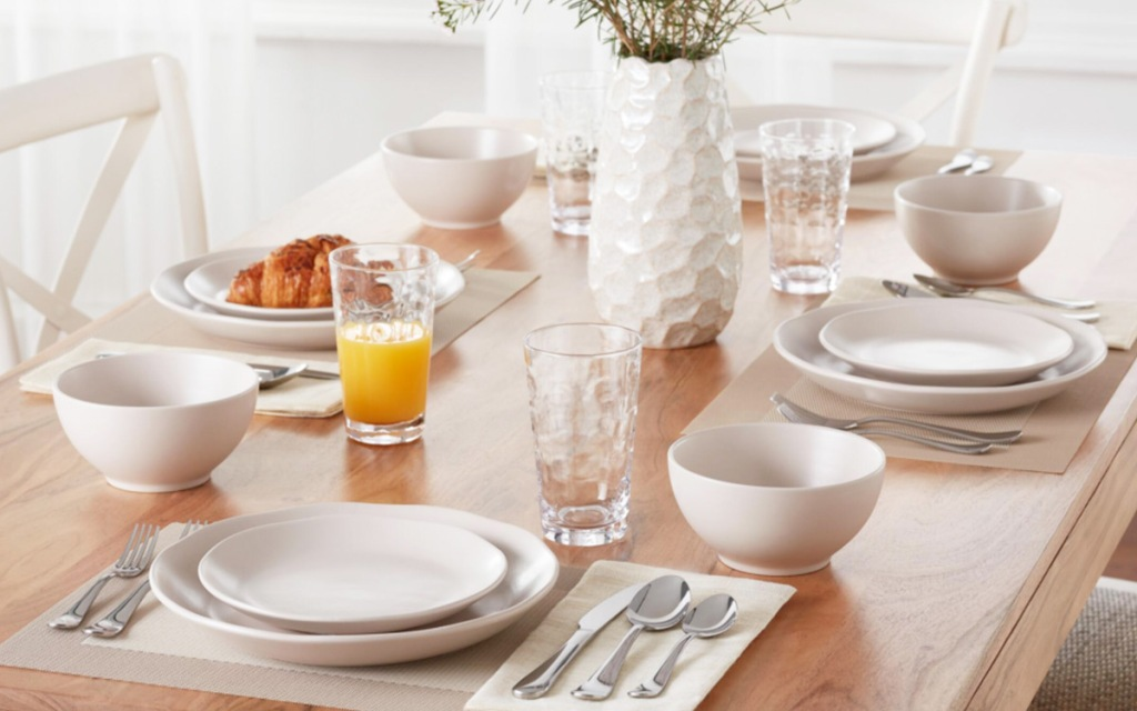 white set of dinnerware on wooden table with white vase of flowers in center