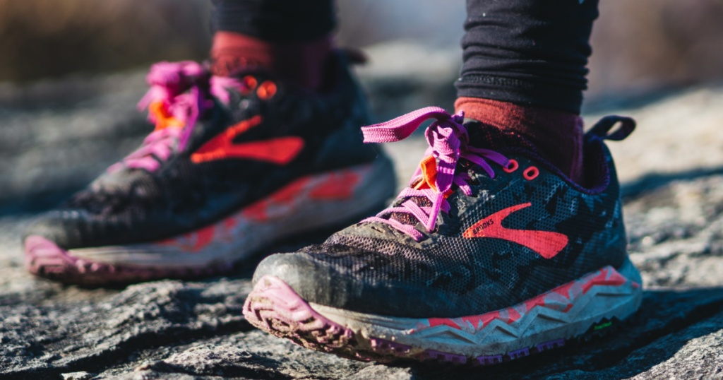 person stranding on ground outdoors wearing black and pink running shoes