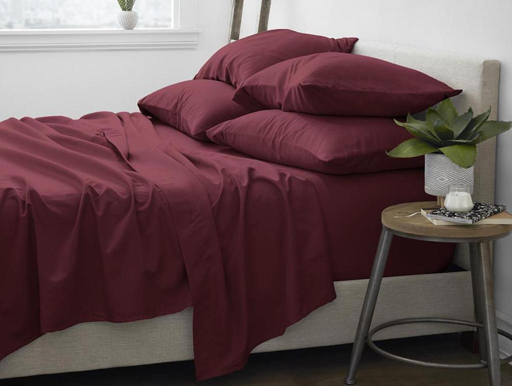side view of burgundy sheets on bed in room