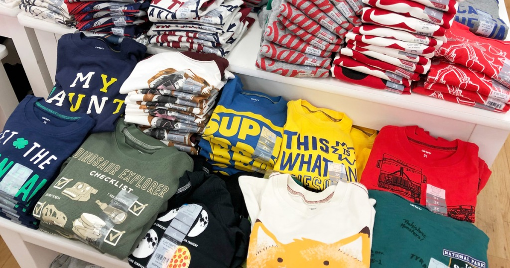 store display table full of folded boys graphic tees