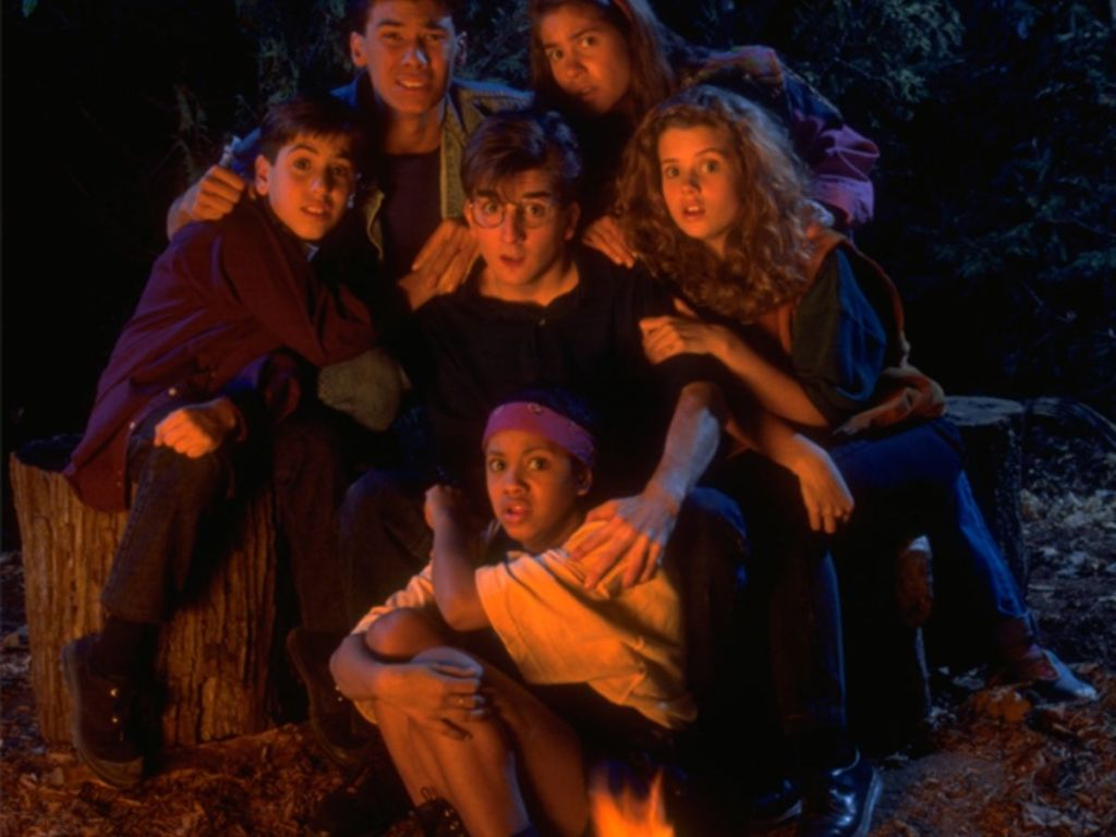 six kids looking scared in front of a campfire
