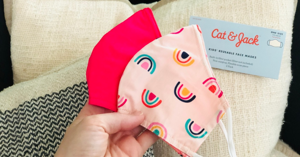 hand holding light pink with rainbows face mask and hot pink face mask from cat and jack