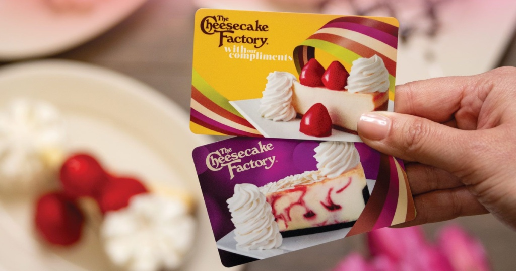 woman's hand holding two Cheesecake Factory gift cards with plates of cheesecake in background