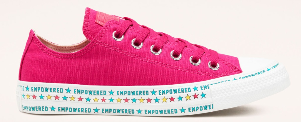 """pink canvas converse shoe with white rubber toe and sole that has the word """"empowered"""" printed along it"""