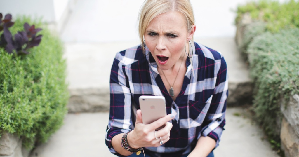 woman sitting outside looking at iPhone