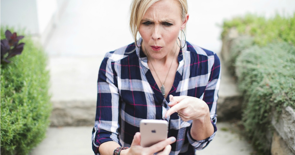 woman looking at iphone pointing to screen