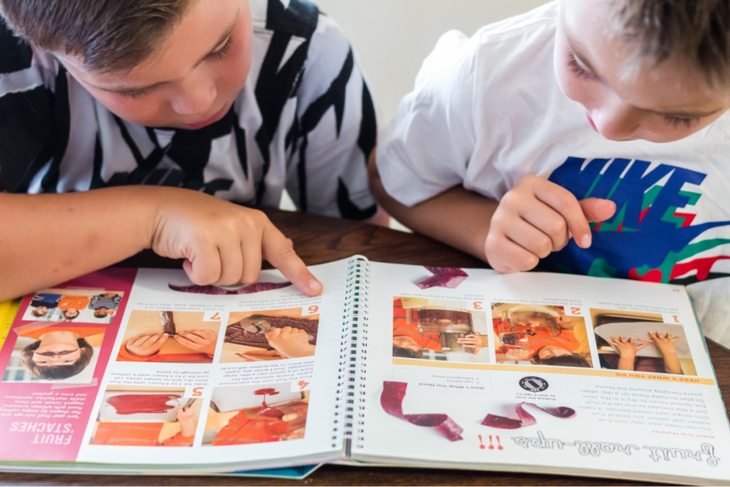 2 boys reading directions in cookbook
