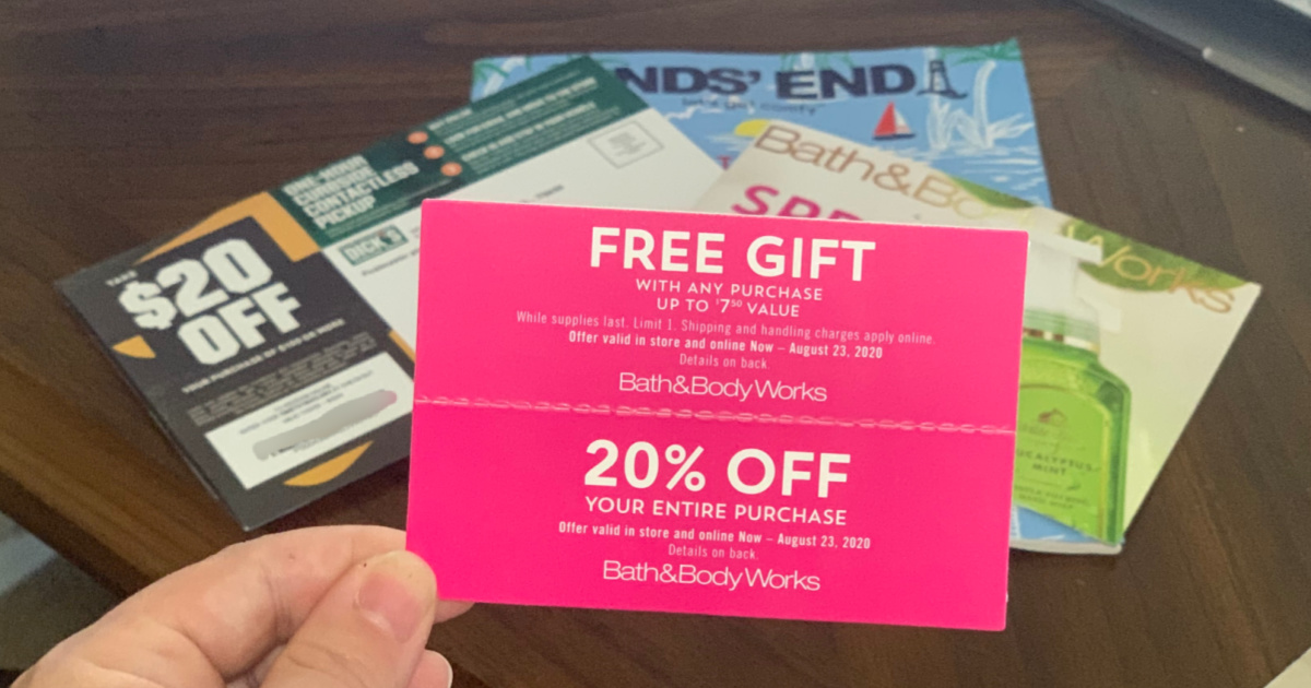 hand holding various mailed coupons