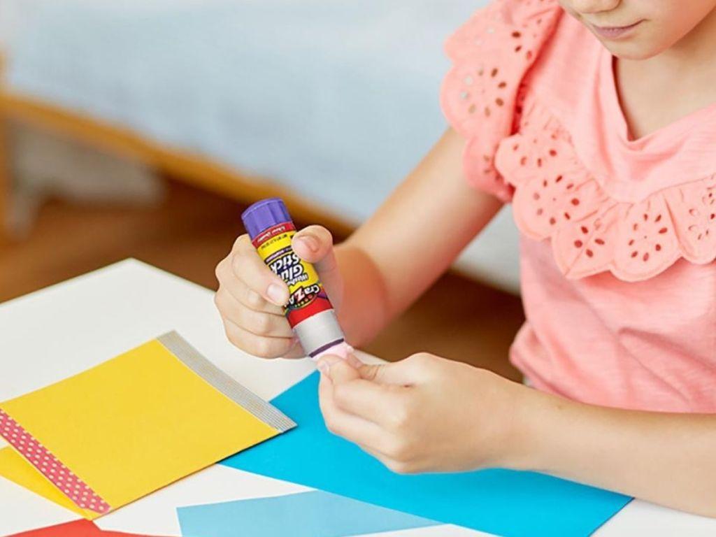 girl using glue stick