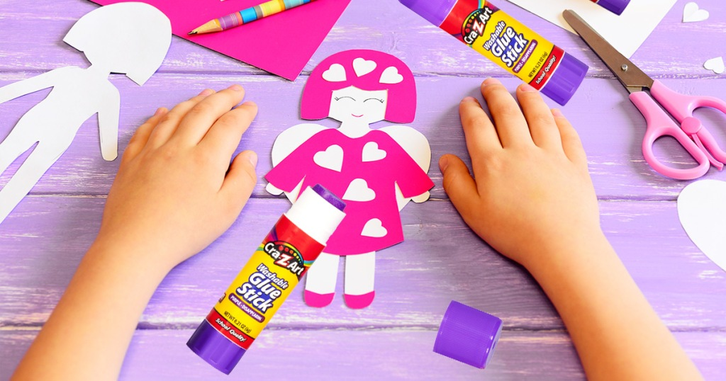 kid using purple glue stick to glue together a pink paper angel on a purple background