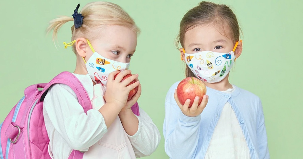 two girls holding apples and wearing crayola theme face masks