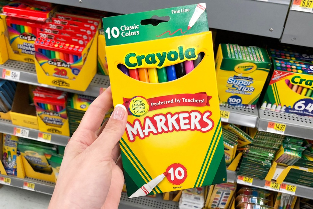 person holding up yellow box of crayola fine line markers