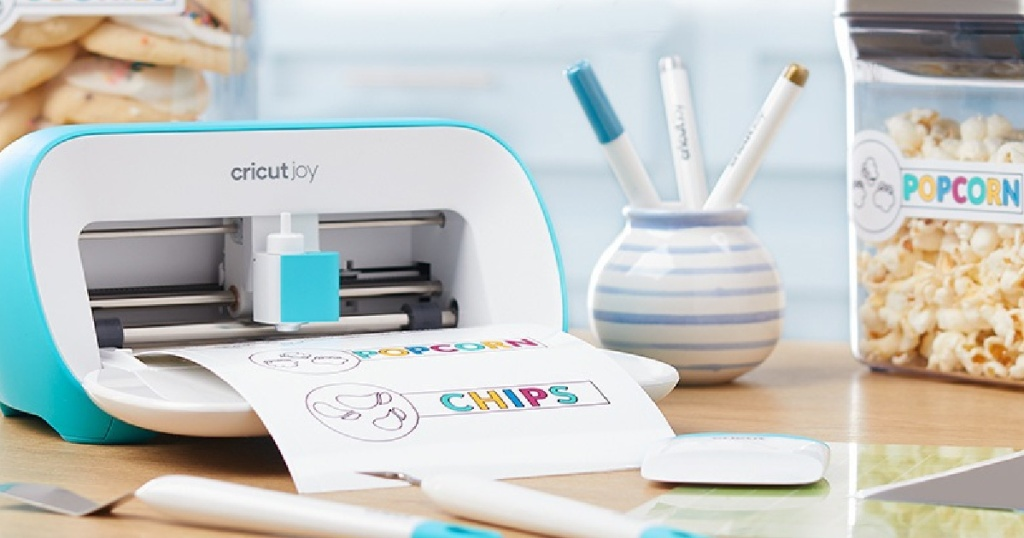 Cricut Joy printing out a colorful sheet of paper next to markers and popcorn snacks