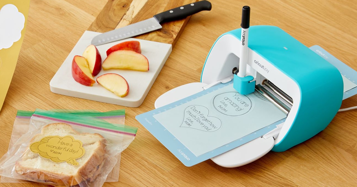 Cricut Joy sitting on a countertop next to sliced apples and Sandwiches