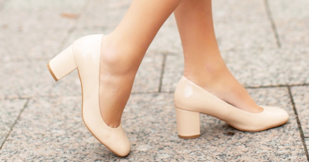 woman walking on pavement in taupe colored pumps with block heels