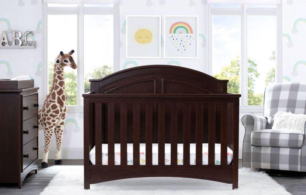nursery with large giraffe, crib, chair and dresser