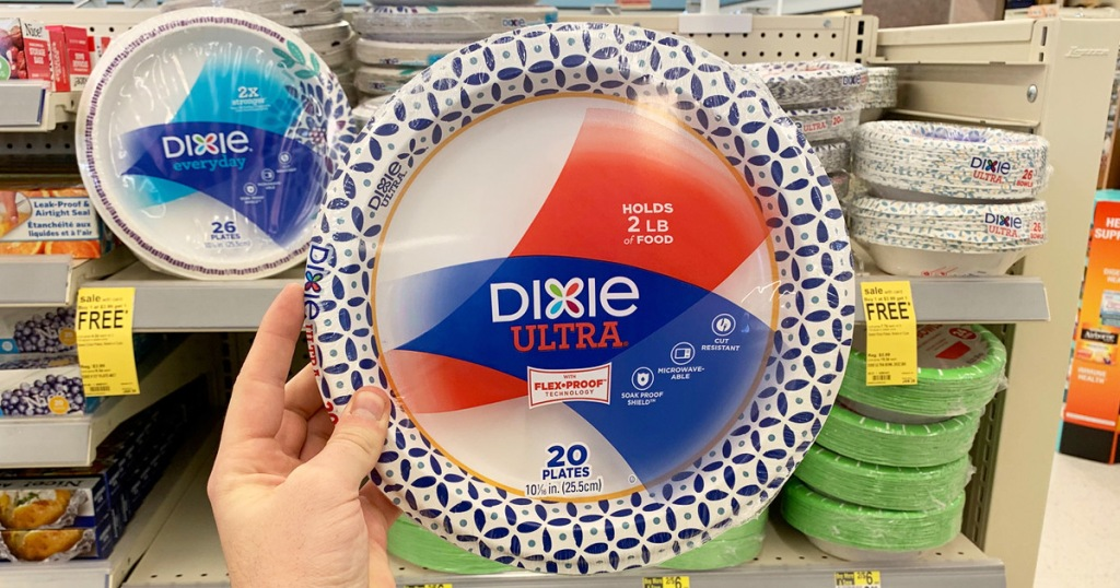 person holding up a pack of dixie paper plates in front of shelf of other paper plates
