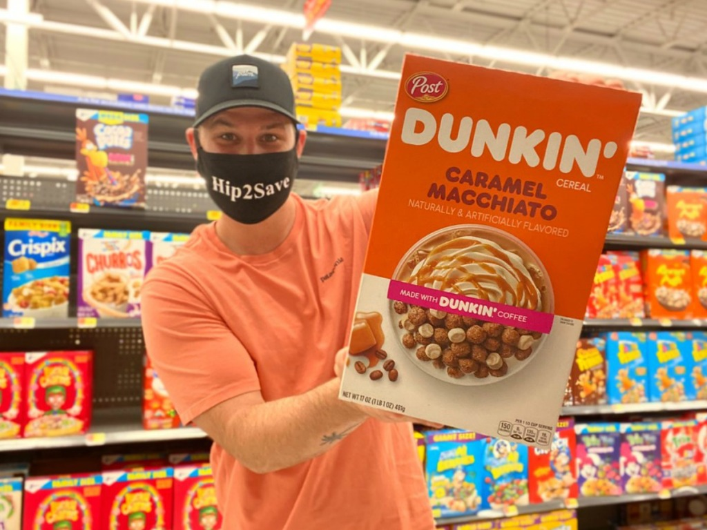 a man holding Dunkin cereal in a store