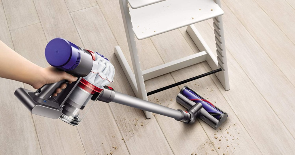 Stick Vacuum Cleaner hand using dyson vacuum to clean mess around high chair