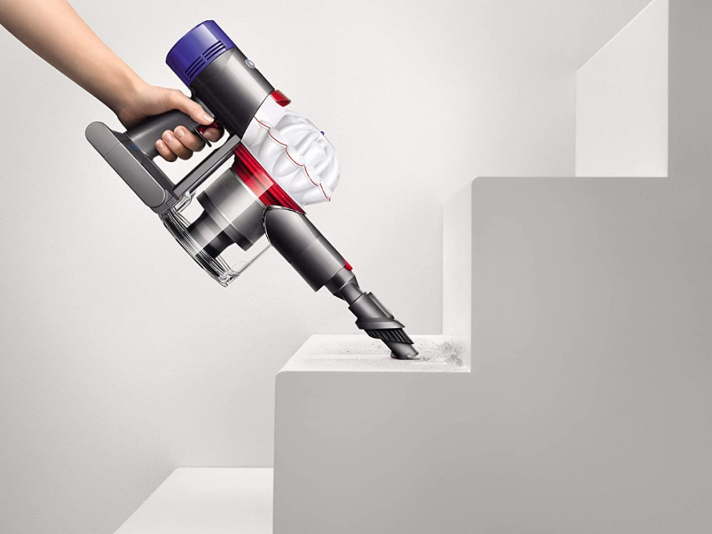 Stick Vacuum Cleaner hand using vacuum to clean stairs