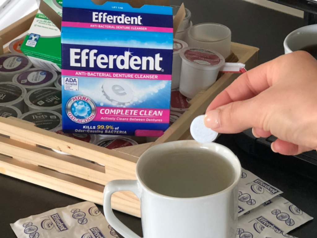 hand putting denture cleaning tablet into white mug with box of denture cleaning tablets and other items on counter in home