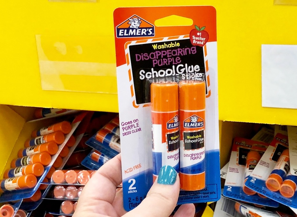 person holding up 2-pack package of elmers disappearing purple glue sticks