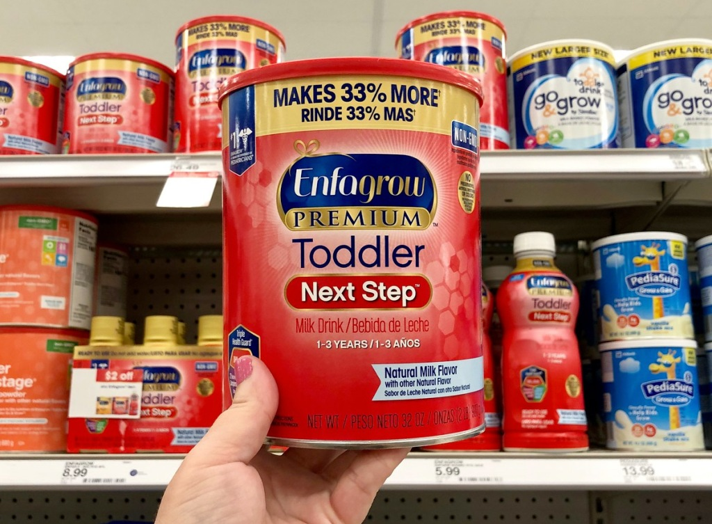 person holding up a large red can of enfagrow toddler powder in front of infant formula aisle in store