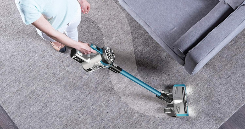 Stick Vacuum Cleaner woman using grey and blue stick vacuum cleaner on grey rug around grey couch