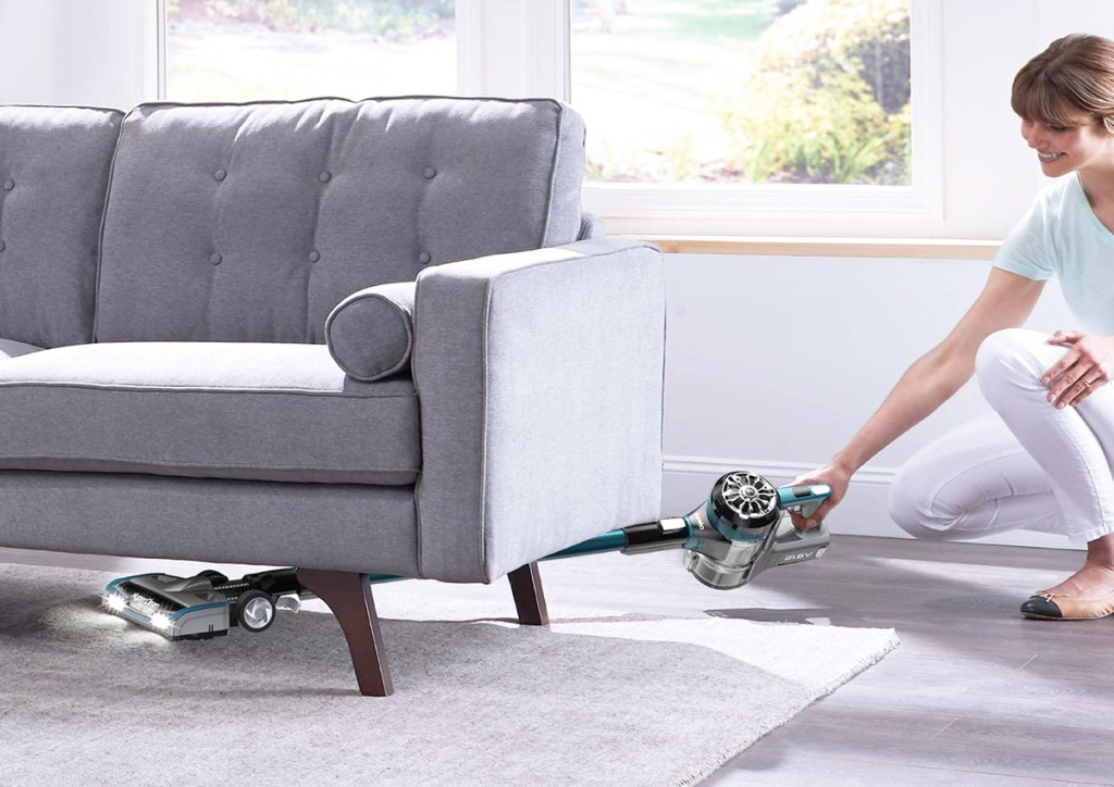 Stick Vacuum Cleaner woman crouching down to reach vacuum cleaner under grey couch