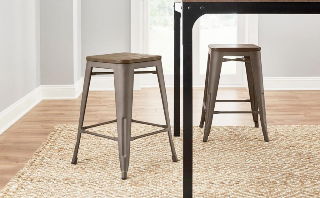 two brown metal backless barstools with wooden seats