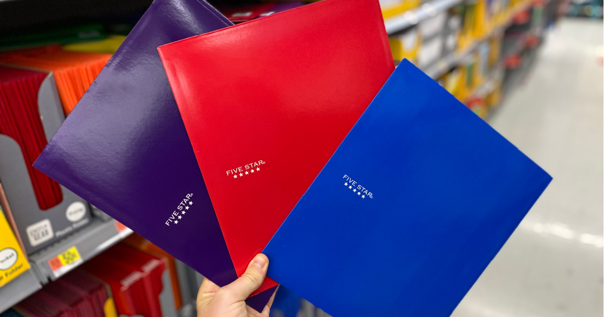 hand holding purple, red, and blue folders in store aisle