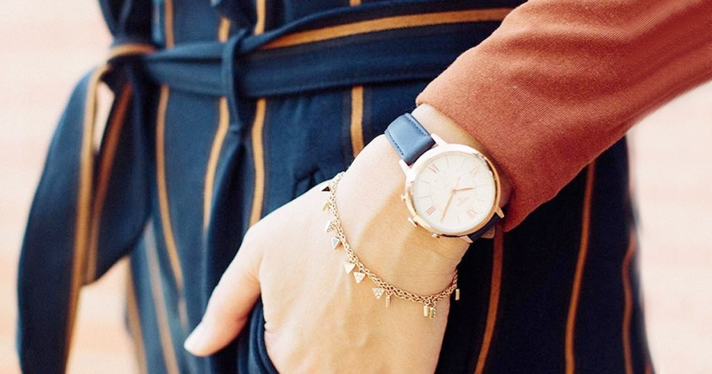 woman wearing navy blue with orange striped pants and orange top with hand in her pocket, wearing a rose gold and navy blue fossil watch on her wrist