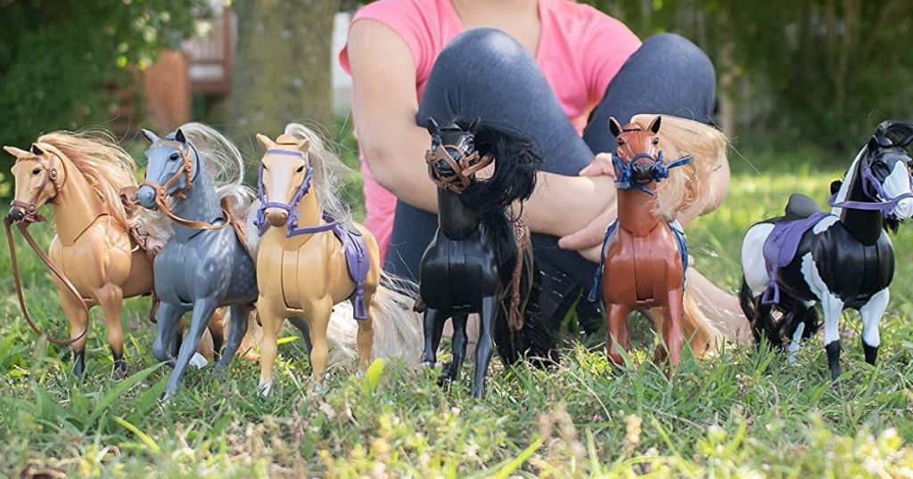Horse toys lined up in front up in front a little girl