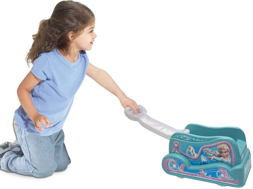 little girl pulling a small plastic wagon