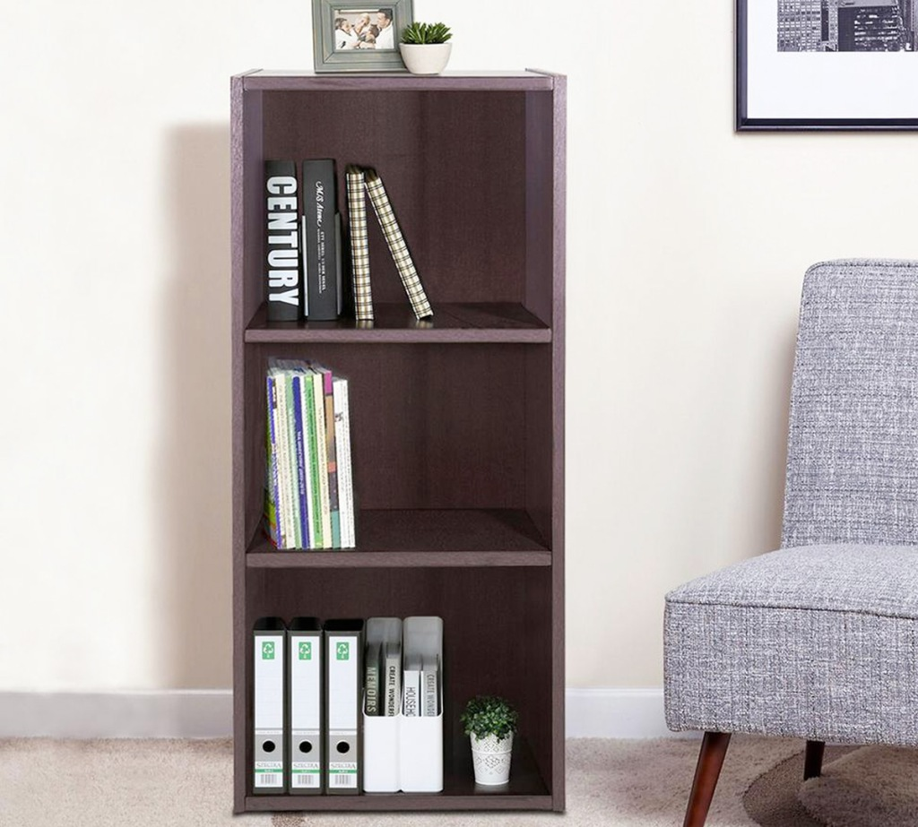 brown wood 3 tier bookcase with books on each shelf near a grey accent chair