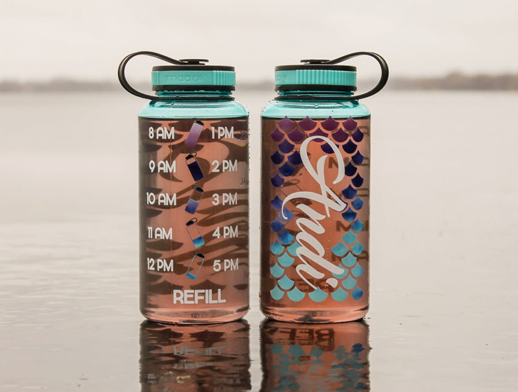 front and back views of mermaid themed water tracker bottles in sand at beach