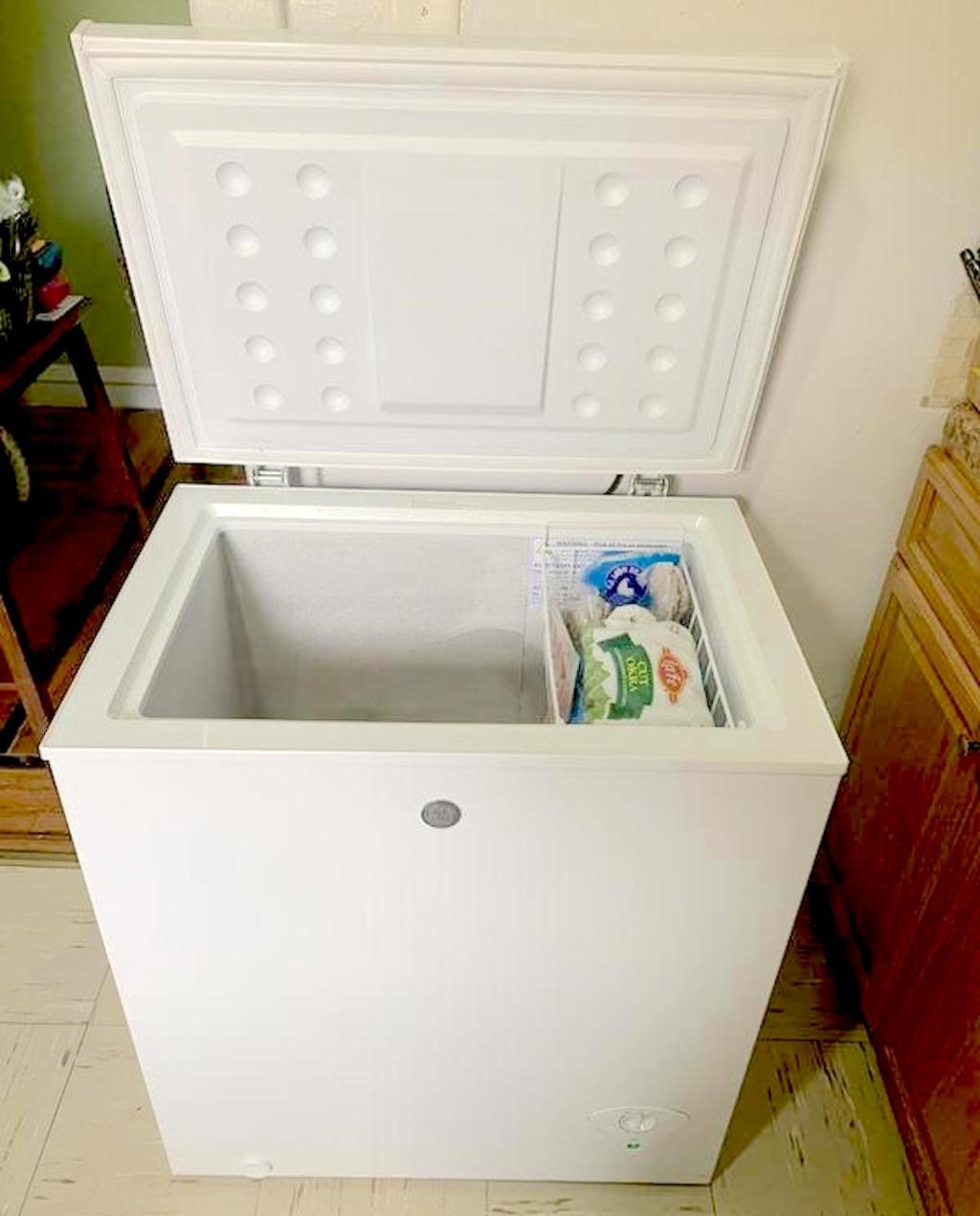 small white deep freezer sitting on floor with lid open
